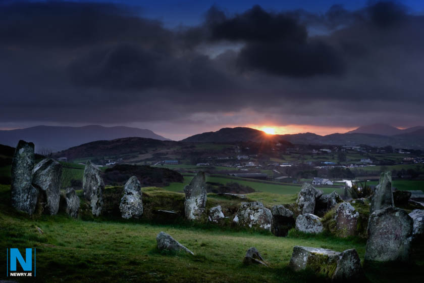 The sun rises behind Ballymacdermot Court Tomb near Newry. The three chambered burial chamber can be dated to at least 2500BC. Photograph: Columba O'Hare/ www.newry.ie