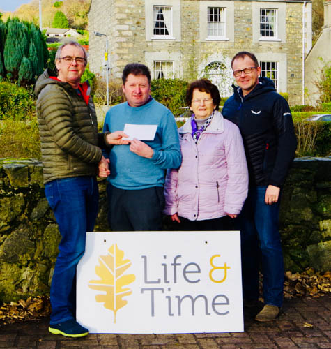 James and Brigid Rice, Rostrevor, present Henry McLaughlin and John McGinn of Life and Time with a donation to the group.