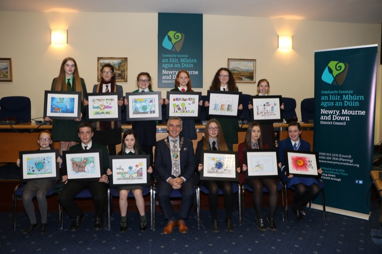 Chairman Newry, Mourne and Down Council, Councillor Mark Murnin with the School's Environmental Calendar Poster Competition Winners. back row l-r July Winner Saoirse Byard Sacred Heart Grammar School Newry, Save Our Seas, August Winner Yasmin Muldrew Newry High School, Beat the Litter, September Winner Maria Loughlin Saint Ronan's Primary School Newry, Ready - Set - Recycle, October Winner Katie Fitzpatrick Holy Cross Primary School Kilkeel, Halloween, November Winner Anna Whewell Down High School Downpatrick, Bin Waste, December Winner Leah Lennon Saint Patrick's Primary School Cullyhanna, Don't Litter and Make Christmas Bitter. Front row l-r January Winner Katie O'Hare Saint Colman's Primary School Saval, Reduce, Reuse, Recycle, February Winner Don Farrell Saint Joseph's Boys High School Newry, Global Warming is leaving the animals homeless, March Winner Larissa Gaffney Carrick Primary School Burren, Water Police, Chairman Newry, Mourne and Down District Council, Councillor Mark Murnin, Front Cover Winner, Charlotte Doyle The High School Ballynahinch, Be a Part of the Solution, Not Part of the Polution, April Winner Holly Black Kilkeel High School Kilkeel, The Earth Does Not Belong to Us, We Belong to the Earth, May Winner Emile Egan Assumption Grammar School Ballynahinch, Save Our Bees.  (missing from photo June Winner Ella McCartney Saint Patrick's Primary School Crossmaglen, Save Our Earth