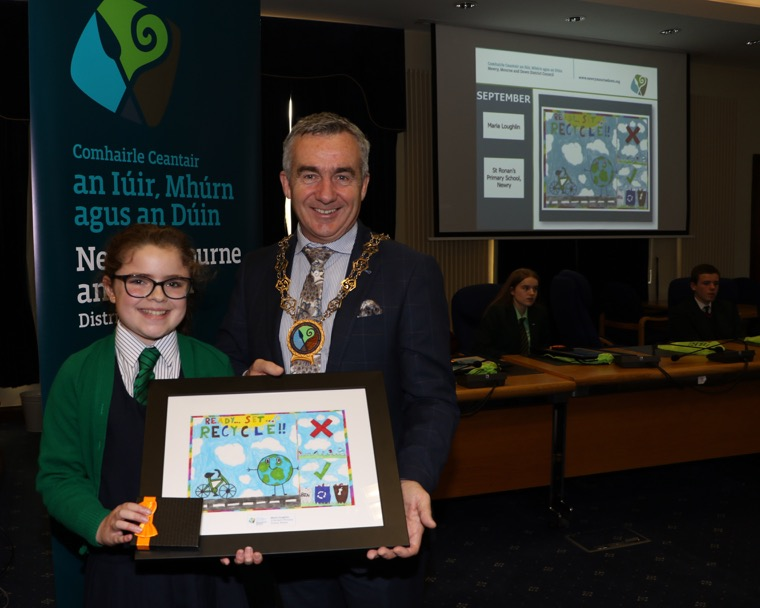 Chairman Newry, Mourne and Down Council, Councillor Mark Murnin with the School's Environmental Calendar Poster September Winner Maria Loughlin Saint Ronan's Primary School Newry.