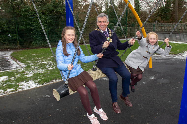 Newry, Mourne and Down District Council Chairman, Mark Murnin with Aine Hughes and Emily Black from St Malachy's Primary School, Camlough at the opening of Oliver Plunkett Play Park.
