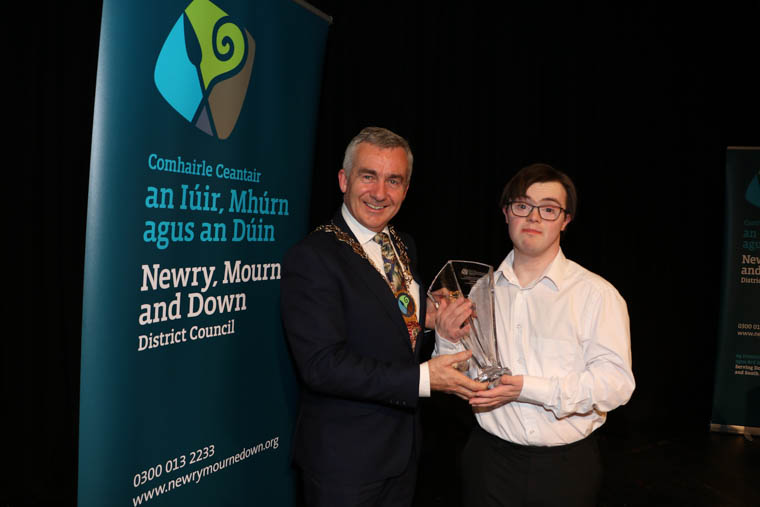 Chairman Newry, Mourne and Down District Council, Councillor Mark Murnin presents Ryan Bogues with his Award. Ryan runs a fantastic cookie box business where he prepares buns, cookies and cakes and places them in an honesty box at his gate.
