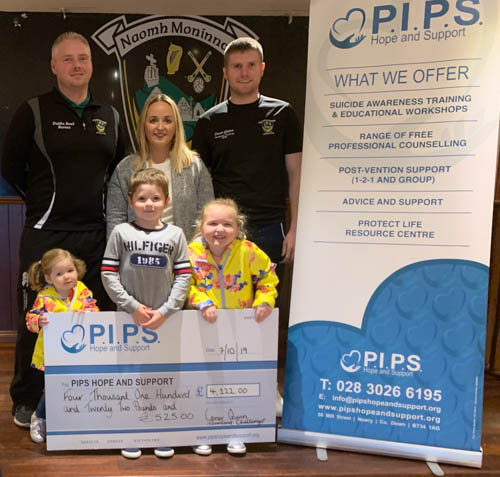 Members of the Quinn family present a cheque to PIPS Hope and Support.