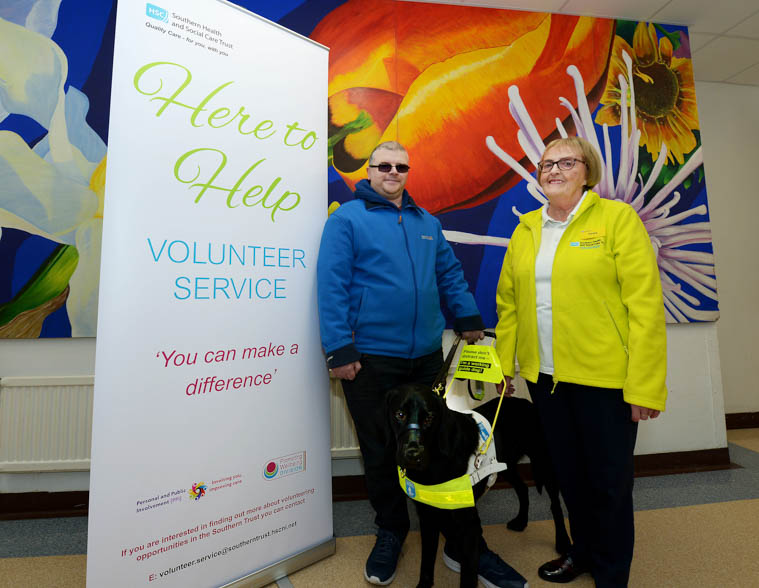 The Southern Trust introduced bright yellow fleeces for our 'Here to Help' volunteers following feedback from service user Leslie Massey. Mr Massey is pictured with his guide dog Munroe and 'Here to Help' volunteer Emma Marshall wearing the new fleece.