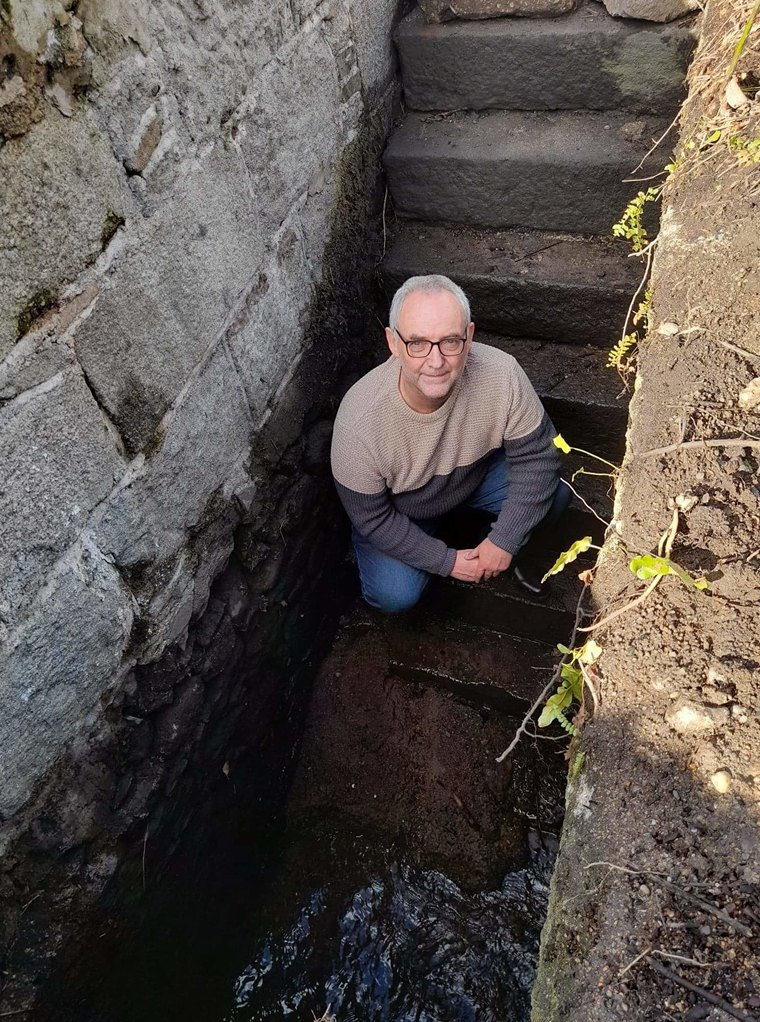 John McCabe investigating the hidden stream and stone structure.