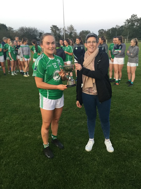 Louise Kenny, Shane O'Neill's Captain, receives the senior league winners trophy from Sinead Reel