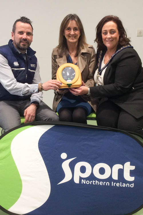 Conleth Donnelly, Sport NI, Carol McMenimin, Murlough Athletics Club and Gillian Fitzpatrick Chairperson NMDDC with one of the defibrillators distributed to local sports clubs.